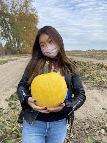 Photo of Audrey Lee holding a pumpkin in a field.